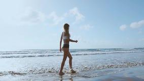Pie desnudo de la mujer que camina en la playa del verano ciérrese encima de la pierna de la mujer joven que camina a lo largo de almacen de metraje de vídeo