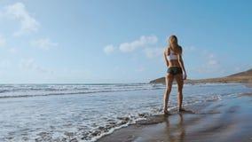 Pie desnudo de la mujer que camina en la playa del verano ciérrese encima de la pierna de la mujer joven que camina a lo largo de metrajes