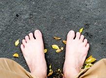 Pie desnudo en piedra negra y las hojas secadas Fotografía de archivo