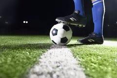 Pie en balón de fútbol en la noche Fotografía de archivo libre de regalías