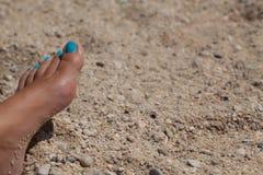 Pie femenino con pedicura ciánica en arena de la playa Fotos de archivo libres de regalías