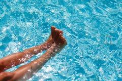 Pie femenino en agua azul Imagen de archivo