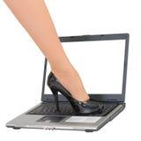 Pie femenino en el teclado de la computadora portátil - juego encima Imagen de archivo libre de regalías