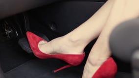 Pie femenino en los tacones altos que empujan el pedal de freno del coche metrajes