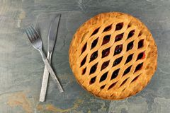 Pie with fork and knife on a grey slate background Stock Image
