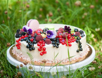 Pie with fresh berries. Pie decorated with fresh berries against a flowers and macaroons Stock Images