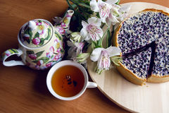 Pie from fresh blueberries sprinkled with coconut. And standing on a wooden stand, standing next to a porcelain teapot with white Cup tea with flowers Royalty Free Stock Photo