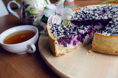 Pie from fresh blueberries sprinkled with coconut. And standing on a wooden stand, standing next to a porcelain teapot with white Cup tea with flowers Royalty Free Stock Photos