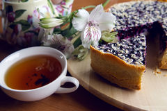 Pie from fresh blueberries sprinkled with coconut. And standing on a wooden stand, standing next to a porcelain teapot with white Cup tea with flowers Stock Photos