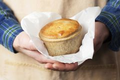 A pie is held in a Baker`s hands. A Baker wearing a khaki apron and blue checkered shirt holds a meat pie in both hands royalty free stock photography