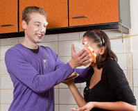 Pie in her face. Young men putting a cream pie in his girlfriend's face Royalty Free Stock Images