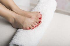 Pie hermoso con pedicura roja del gel en el rollo blanco de la toalla Imagenes de archivo