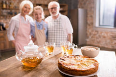 Pie and hot tea on table. With family behind, focus on foreground Royalty Free Stock Photos