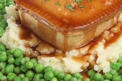 Pie, Mash & Peas. Steak pie with mashed potato, peas and gravy Royalty Free Stock Photo