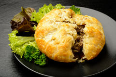 Pie with minced meat on black plate. Stock Image