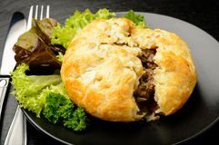 Pie with minced meat on black plate. Royalty Free Stock Images
