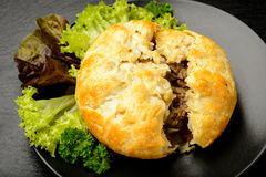 Pie with minced meat on black plate. Royalty Free Stock Photo