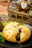 Pie with minced meat on black plate. Stock Photo