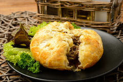 Pie with minced meat on black plate. Stock Images