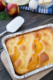 Pie with peaches. On an old wooden table with green leaves, rustic style Royalty Free Stock Photo