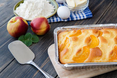 Pie with peaches. On an old wooden table with green leaves, rustic style Stock Image