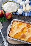 Pie with peaches. On an old wooden table with green leaves, rustic style Stock Photo