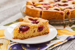 Pie with plums and slice and cup with coffee Stock Photo