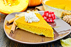 Pie pumpkin in brown plate with cream on dark board Royalty Free Stock Images