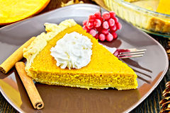 Pie pumpkin in plate with cream on dark board Royalty Free Stock Image