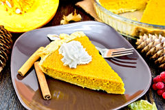 Pie pumpkin in plate with whipped cream on board Royalty Free Stock Image