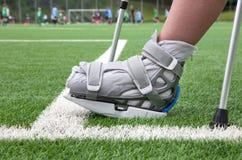 Pie quebrado, muletas - lesión de los deportes imagenes de archivo