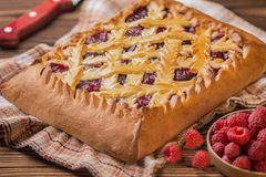Pie with raspberries on a wooden table. Next to it lies a knife Stock Images