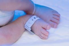 Pie recién nacido del bebé con nombre de la etiqueta del hospital de la identificación fotografía de archivo