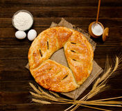 Pie on sacking, wooden background. Baking ingredients: flour, eggs, salt and ears Royalty Free Stock Photography