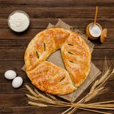 Pie on sacking, wooden background. Baking ingredients: flour, eggs, salt and mug of milk, ears. View from above.  Stock Photography