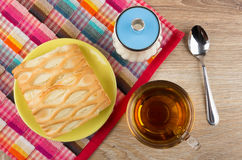 Pie in saucer, sugar bowl on napkin, cup of tea Stock Image