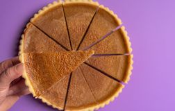Pie slice held in hand over a whole pumpkin pie. Above view royalty free stock photo