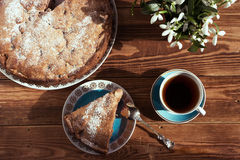 Pie and slice with tea on a brown wooden background.  Selective focus, toned image, film effect, top view Stock Image