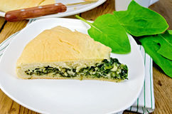 Pie with spinach and cheese on the board with leaves Royalty Free Stock Photos