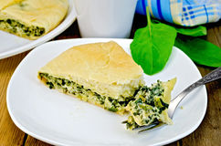 Pie with spinach and cheese with a fork on a board Royalty Free Stock Images