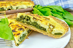 Pie with spinach and cheese in plate on board Royalty Free Stock Photography