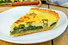 Pie with spinach and cheese in plate on table Stock Photos