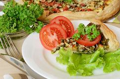 Pie with spinach and cheese. Served with salad and tomatoes Stock Images
