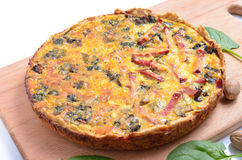 Pie with spinach and ham on the board. Isolated. Pie with spinach and ham on the board. Isolated Stock Images