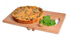 Pie with spinach and ham on the board. Isolated Royalty Free Stock Image