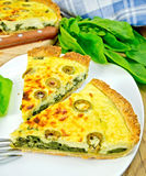 Pie with spinach and olives in plate on board Stock Image