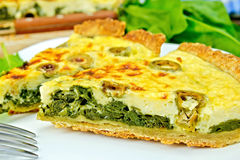 Pie with spinach and olives on plate Stock Images