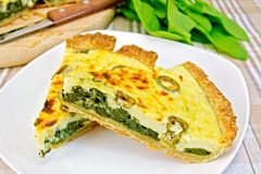 Pie with spinach in plate on fabric Royalty Free Stock Photos