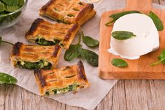 Pie with spinach and ricotta cheese. Pie with spinach and ricotta cheese on wooden table stock photo