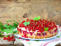 Pie or sponge cake with red currants and poppy seeds. On a wooden background Royalty Free Stock Image